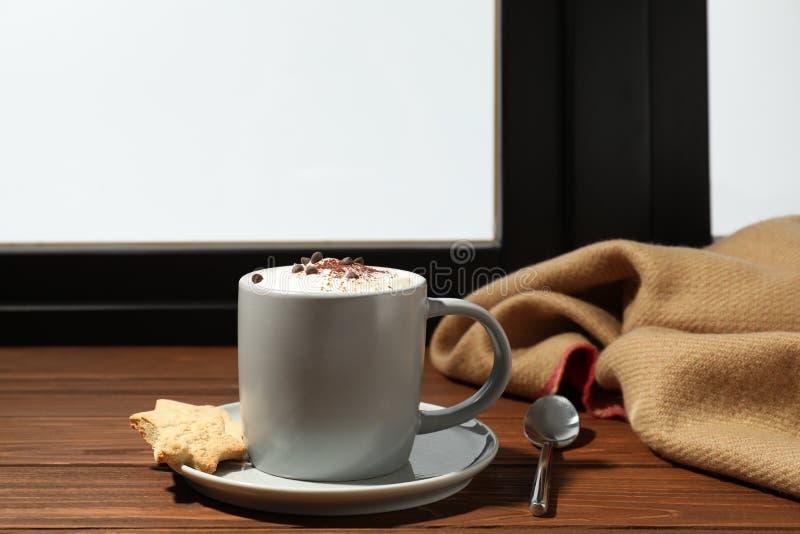 Φλυτζάνι του cappuccino με τα μπισκότα στο windowsill, διάστημα για το κείμενο Χειμερινό ποτό στοκ φωτογραφίες με δικαίωμα ελεύθερης χρήσης