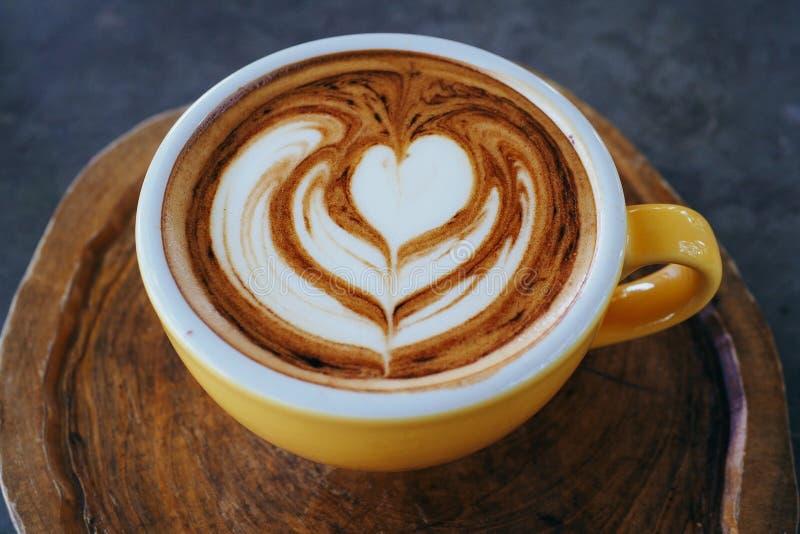 Φλυτζάνι του cappuccino με την όμορφη τέχνη latte στο ξύλινο πιάτο στοκ εικόνα με δικαίωμα ελεύθερης χρήσης