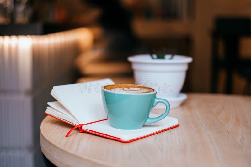 Φλυτζάνι του cappuccino με το σημειωματάριο στοκ εικόνα