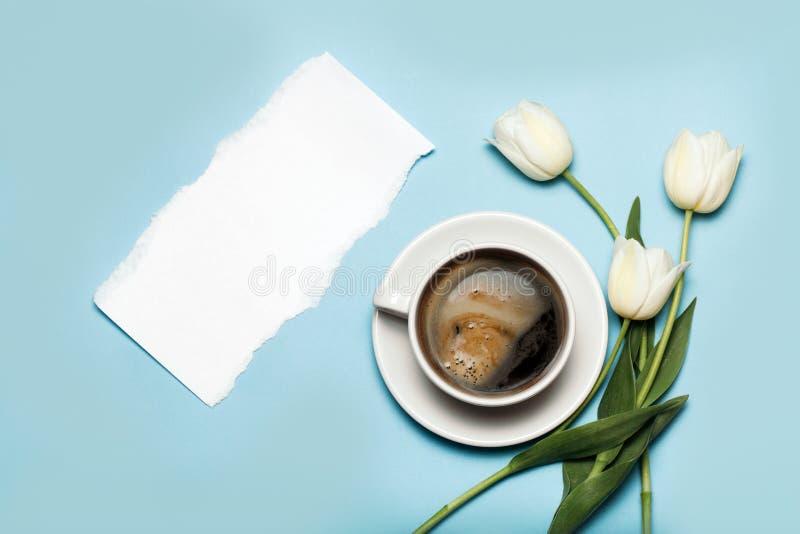 Φλυτζάνι του coffe και των άσπρων τουλιπών στο μπλε υπόβαθρο στοκ φωτογραφία με δικαίωμα ελεύθερης χρήσης