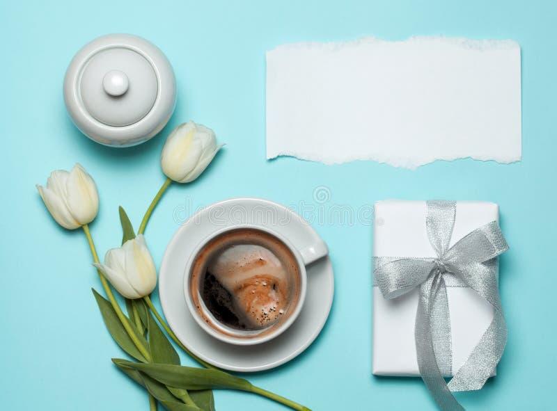 Φλυτζάνι του coffe και των άσπρων τουλιπών στο μπλε υπόβαθρο στοκ φωτογραφία