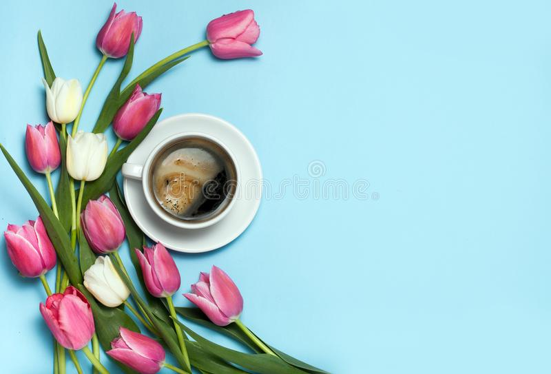 Φλυτζάνι του coffe και των ρόδινων τουλιπών στο μπλε υπόβαθρο στοκ φωτογραφία με δικαίωμα ελεύθερης χρήσης