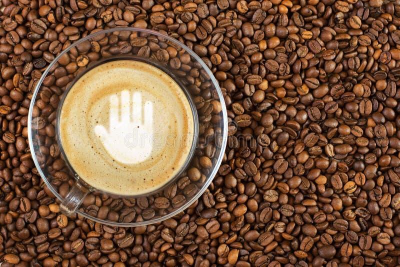 Φλυτζάνι του espresso με το σημάδι χειρονομίας στάσεων στον αφρό καφέ στο υπόβαθρο φασολιών καφέ Με το διάστημα αντιγράφων στοκ φωτογραφία