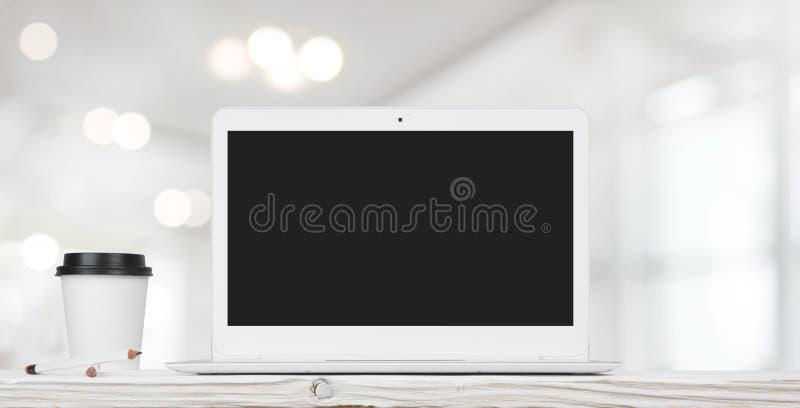 Φλυτζάνι φορητών προσωπικών υπολογιστών και καφέ θολωμένο στο περίληψη εσωτερικό γραφείων στοκ φωτογραφία με δικαίωμα ελεύθερης χρήσης