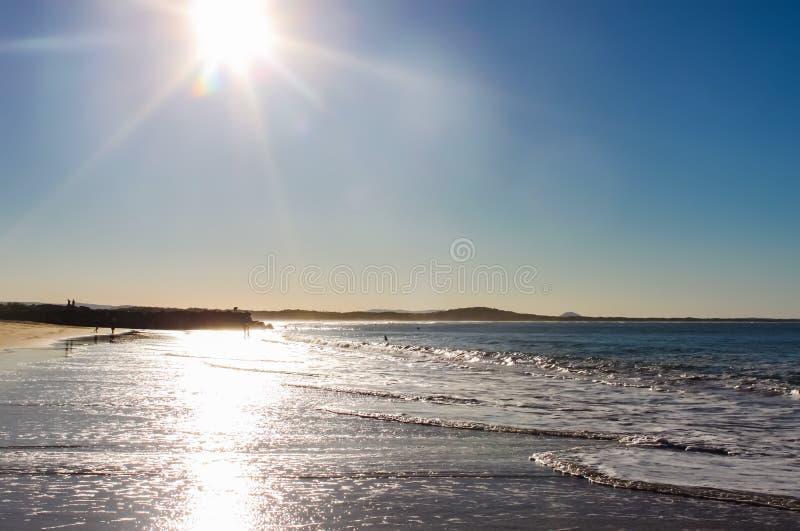 Φλόγα ήλιων στο νερό σε αργά το απόγευμα με τους unrecognizable ανθρώπους στην απόσταση - κεφάλια Αυστραλία Noosa στοκ φωτογραφία