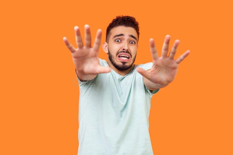 Φοβάμαι! Πορτρέτο τρομαγμένου μελαχρινού ανθρώπου που κάνει φοβισμένη κίνηση με σηκωμένα χέρια απομονωμένο φόντο σε πορτοκαλί στοκ εικόνα με δικαίωμα ελεύθερης χρήσης