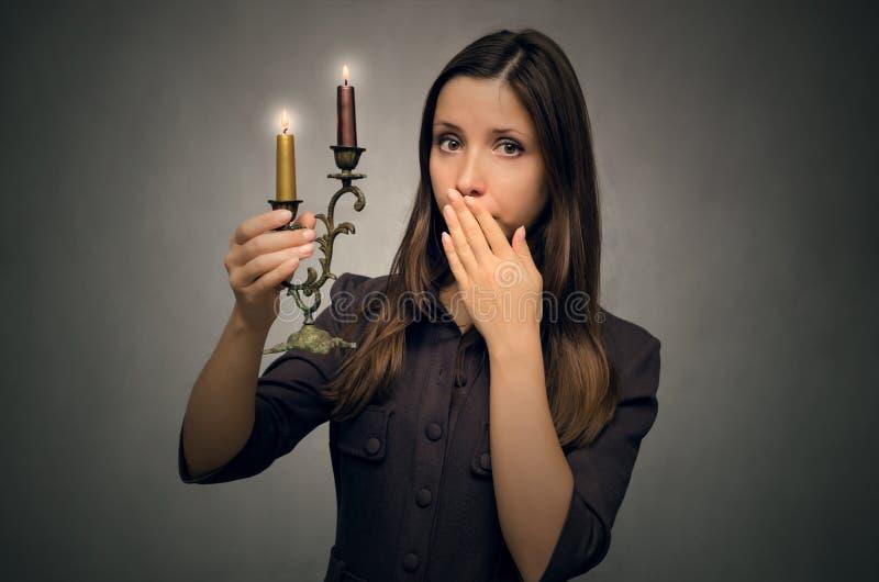 Φοβησμένη γυναίκα με τα κεριά στοκ εικόνες