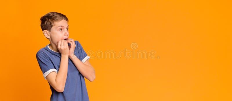 Φοβησμένο αγόρι που καλύπτει το στόμα με τα χέρια, που κοιτάζουν κατά μ στοκ εικόνα