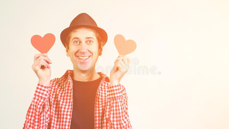 Φοβιτσιάρης τρελλός εύθυμος τύπος που κρατά τις κόκκινες καρδιές Άτομο ερωτευμένο διάστημα αντιγράφων Αστείο άτομο στο πουκάμισο  στοκ εικόνες