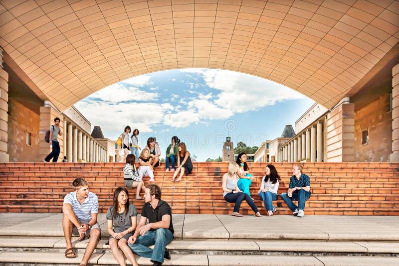 Φοιτητές πανεπιστημίου που έχουν τις συνομιλίες στο πάτωμα εκτός από τα κτήρια στοκ φωτογραφίες με δικαίωμα ελεύθερης χρήσης