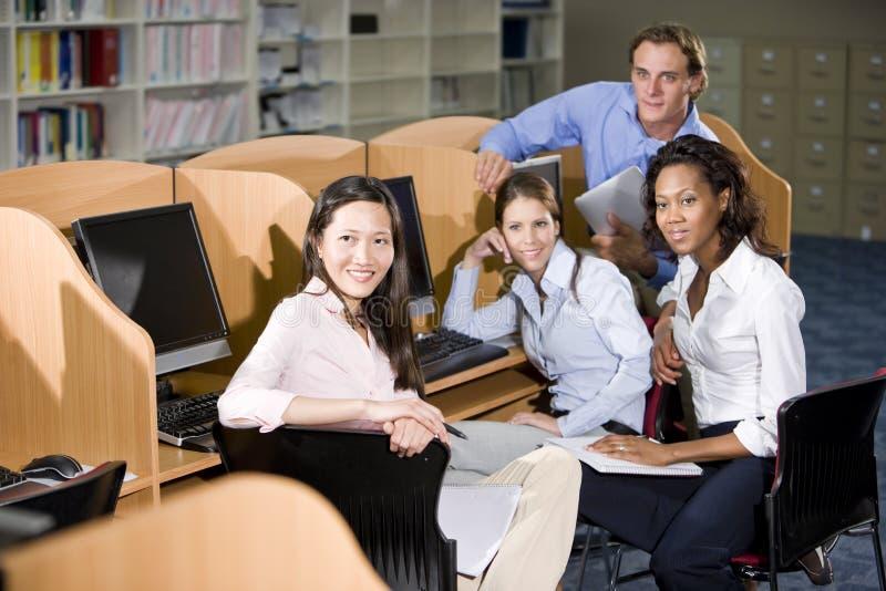 Φοιτητές πανεπιστημίου που κάθονται στον υπολογιστή βιβλιοθηκών στοκ φωτογραφίες