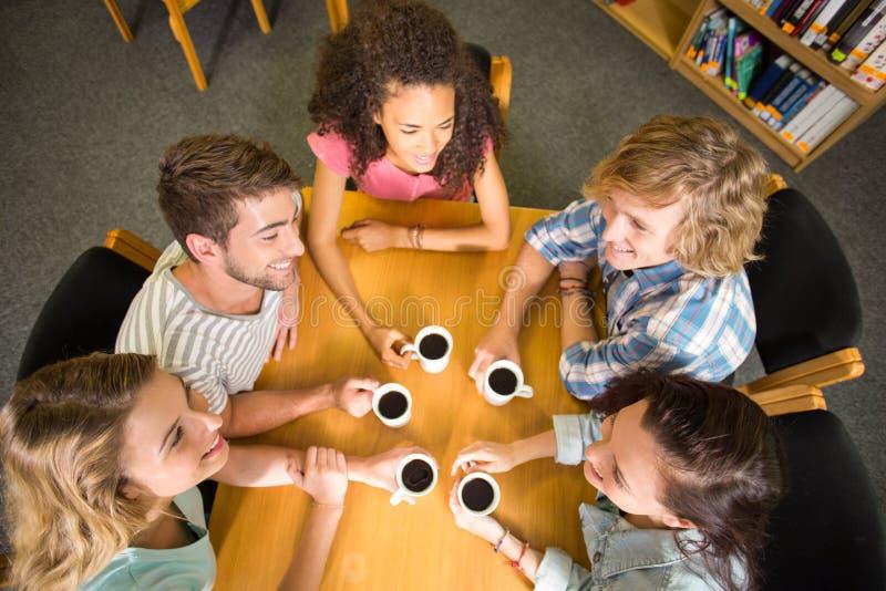Φοιτητές πανεπιστημίου που κρατούν τις κούπες καφέ στον πίνακα στοκ εικόνες