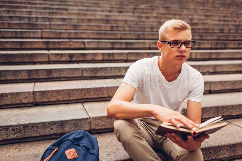Φοιτητής πανεπιστημίου με τη συνεδρίαση βιβλίων ανάγνωσης σακιδίων πλάτης στα σκαλοπάτια και τα γυαλιά εκμετάλλευσης Τύπος που με στοκ εικόνες με δικαίωμα ελεύθερης χρήσης