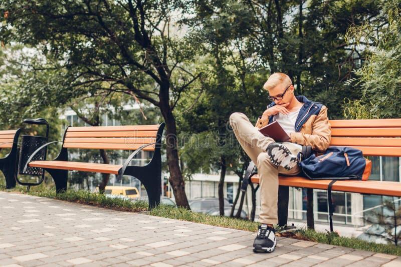 Φοιτητής πανεπιστημίου με το βιβλίο ανάγνωσης σακιδίων πλάτης που περπατά στη συνεδρίαση πάρκων φθινοπώρου στον πάγκο στοκ φωτογραφία