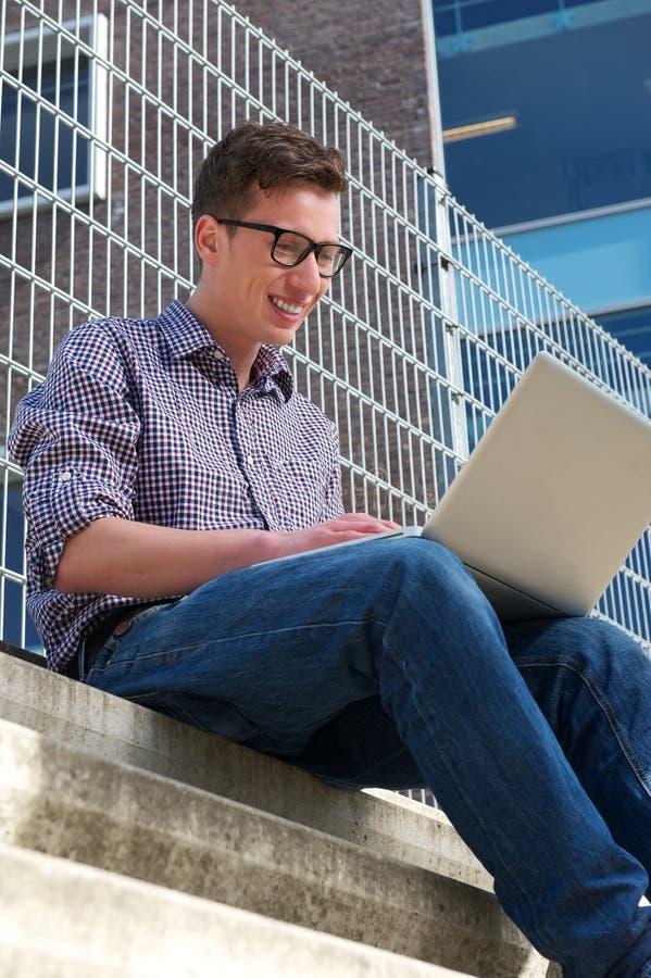 Φοιτητής πανεπιστημίου που εργάζεται στο lap-top υπαίθρια στοκ εικόνες
