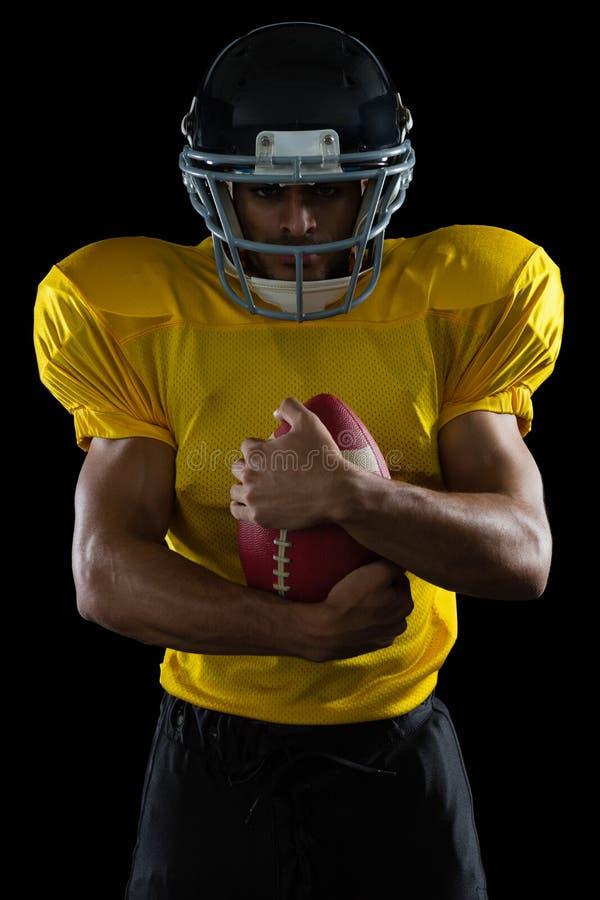 Φορέας αμερικανικού ποδοσφαίρου που κρατά μια σφαίρα και στα δύο μπράτσα του στοκ εικόνες