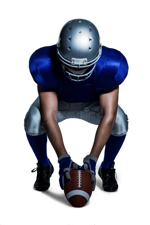Φορέας αμερικανικού ποδοσφαίρου στην ομοιόμορφη σφαίρα εκμετάλλευσης σκύβοντας στοκ φωτογραφία με δικαίωμα ελεύθερης χρήσης