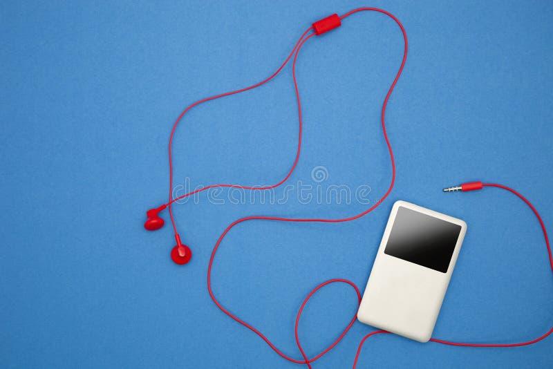 Φορέας μουσικής με το κόκκινο ακουστικό στο μπλε υπόβαθρο εγγράφου στοκ εικόνες