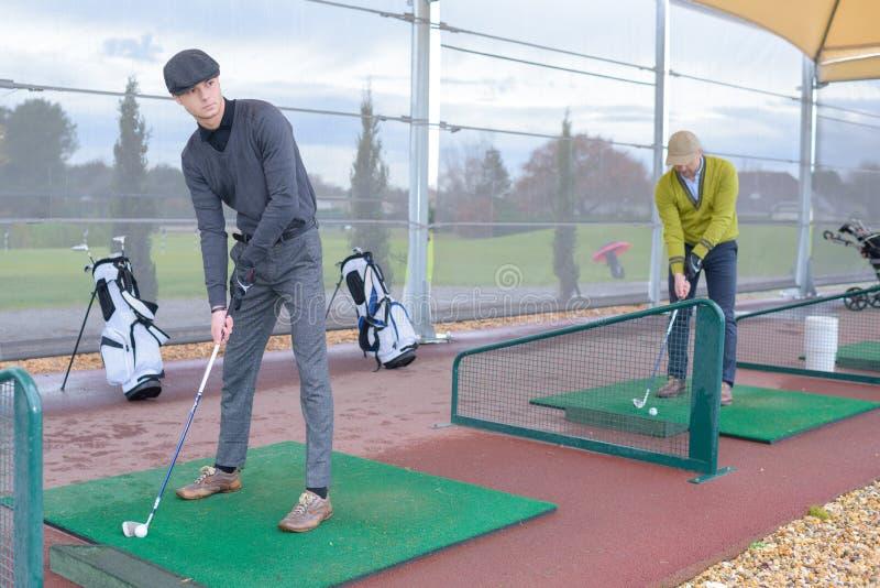 Φορείς γκολφ που χτυπούν τον πυροβολισμό με τη λέσχη στη σειρά μαθημάτων στοκ εικόνες