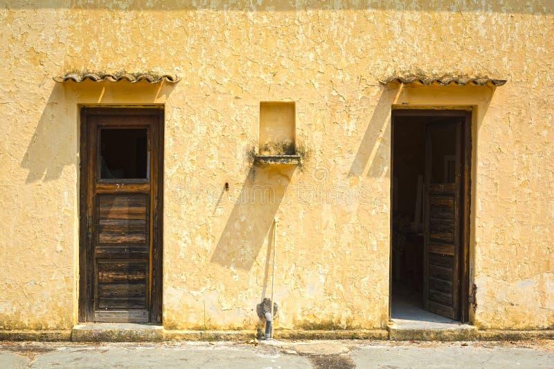 Φορεμένες ξύλινες πόρτες σε έναν ξεπερασμένο τοίχο στοκ εικόνες