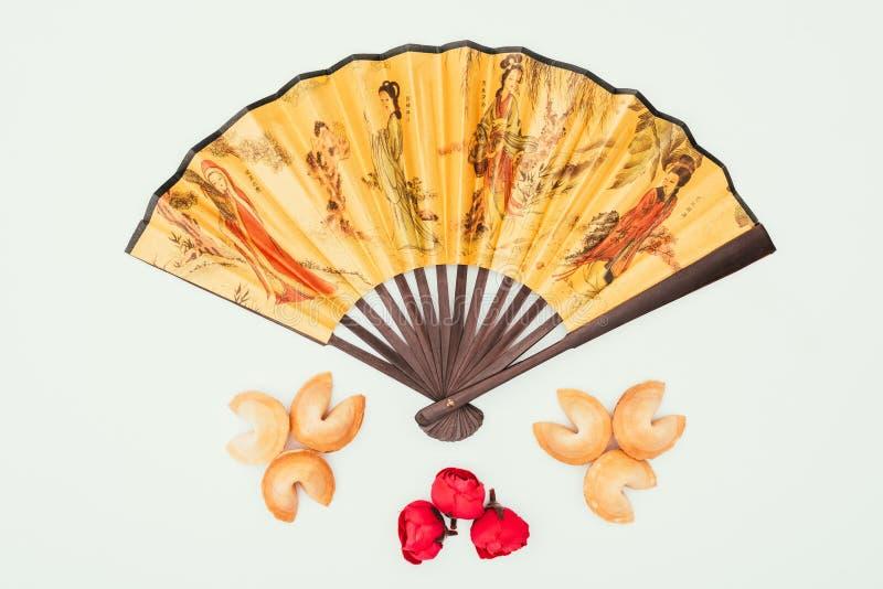 Φορητός ανεμιστήρας παραδοσιακού κινέζικου τα λουλούδια και τα μπισκότα τύχης που απομονώνονται με στο λευκό στοκ φωτογραφία με δικαίωμα ελεύθερης χρήσης