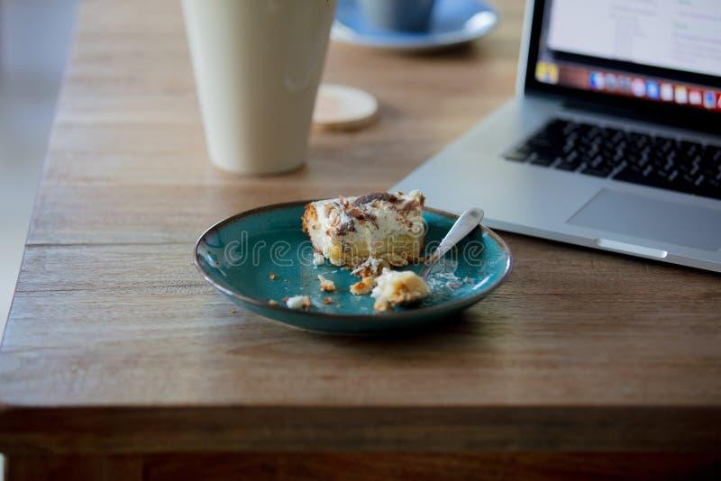 Φορητός υπολογιστής και πιάτο με το κέικ σε ένα talbe στοκ εικόνα