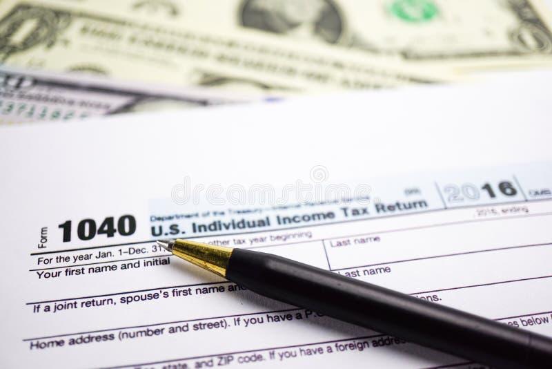 Φορολογική έντυπο φορολογικής δήλωσης 1040 και δολάριο: U S Μεμονωμένο εισόδημα στοκ φωτογραφίες