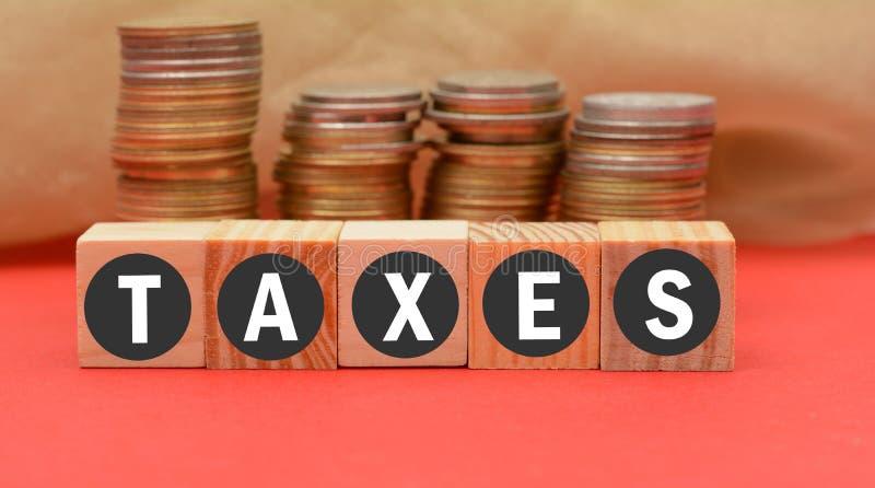 Φορολογική λέξη στους ξύλινους φραγμούς με το νόμισμα στο υπόβαθρο στοκ εικόνες