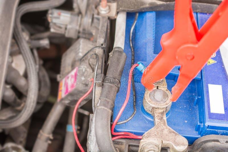 Φορτίζοντας μια μπαταρία αυτοκινήτων με τη φόρτιση του καλωδίου στοκ εικόνα με δικαίωμα ελεύθερης χρήσης
