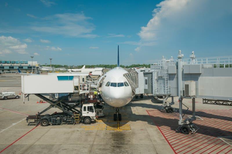 Φορτίο φόρτωσης στο αεροπλάνο στον αερολιμένα πριν από την πτήση Κιβώτιο εμπορευματοκιβωτίων φόρτωσης ελέγχου επιστατών στο αεροπ στοκ εικόνα