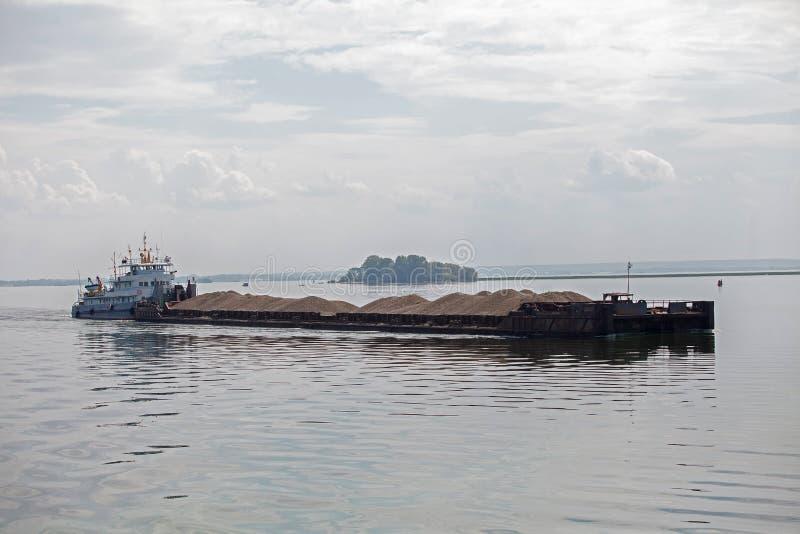 Φορτηγίδα που ωθείται με τη βάρκα ρυμουλκών στον ποταμό στοκ εικόνες