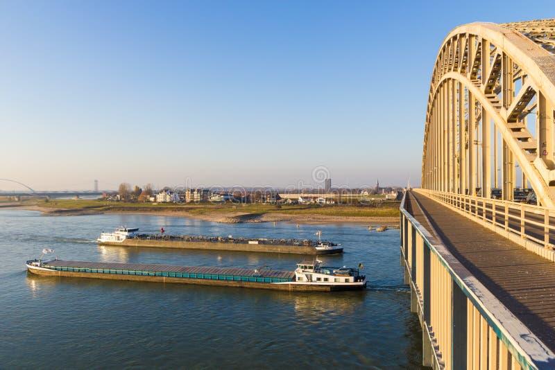 Φορτηγίδες ποταμών φορτίου που περνούν κάτω από τη waal γέφυρα στο Nijmegen στοκ φωτογραφία