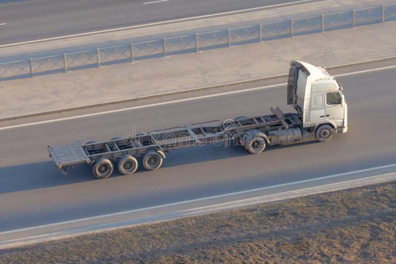 Φορτηγό με ένα κενό μακρύ ρυμουλκό χωρίς φορτίο, που οδηγεί στην εθνική οδό, κορυφή επάνω από την άποψη στοκ εικόνα με δικαίωμα ελεύθερης χρήσης