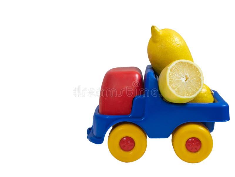 Φορτηγό παιχνιδιών που γεμίζουν με τα κίτρινα λεμόνια για την παράδοση στοκ εικόνες