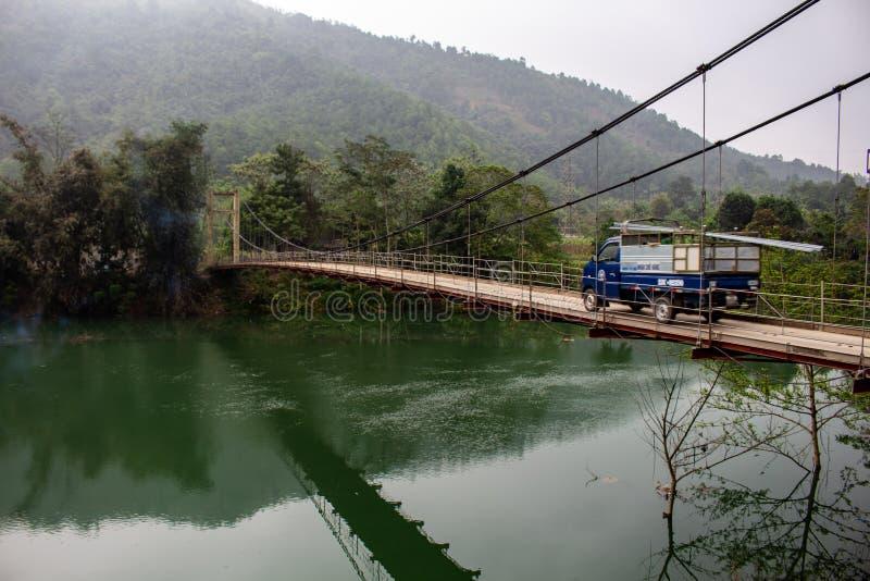 Φορτηγό που περνά πέρα από μια γέφυρα που περιβάλλεται από τη ζούγκλα Βιετνάμ στοκ εικόνες