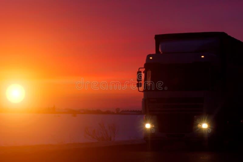 Φορτηγό σκιαγραφιών με το εμπορευματοκιβώτιο στην εθνική οδό, έννοια μεταφορών φορτίου Υπόβαθρο ηλιοβασιλέματος με το διάστημα αν στοκ φωτογραφίες με δικαίωμα ελεύθερης χρήσης