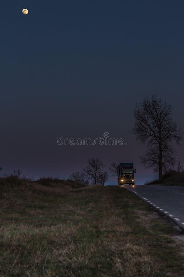 Φορτηγό στο δρόμο και το φεγγάρι στοκ εικόνες με δικαίωμα ελεύθερης χρήσης