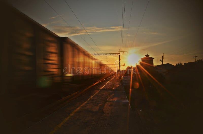 Φορτηγό τρένο στο σταθμό τρένου κατά τη διάρκεια του ηλιοβασιλέματος στοκ εικόνα