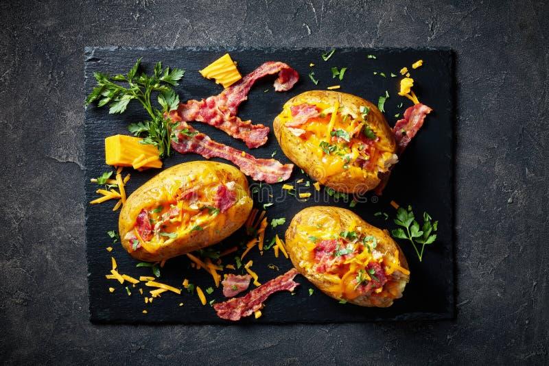 Φορτωμένες ψημένες πατάτες με το μπέϊκον, τυρί, κρέας στοκ εικόνες