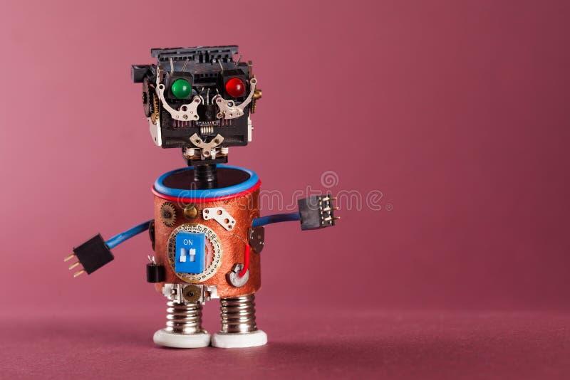 Φουτουριστική έννοια ρομπότ Ο αστείος μηχανισμός παιχνιδιών, μαύρο πλαστικό κεφάλι, χρωμάτισε τα πράσινα κόκκινα μάτια, μπλε χέρι στοκ φωτογραφία με δικαίωμα ελεύθερης χρήσης