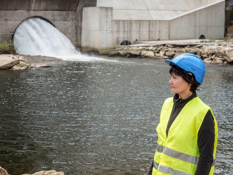 Φράγμα και στρόβιλοι ενός σταθμού υδροηλεκτρικής ενέργειας με τις μειωμένες ροές του νερού και τον εργαζόμενο γυναικών στοκ εικόνα με δικαίωμα ελεύθερης χρήσης