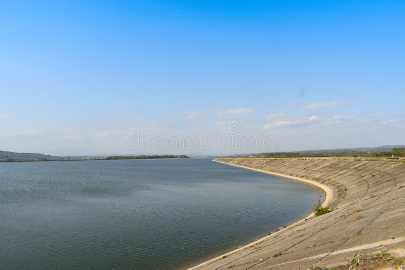 Φράγμα υδρενέργειας στον ποταμό Olt σε μια ηλιόλουστη ημέρα άνοιξη Υδροηλεκτρικές εγκαταστάσεις στην τεχνητή λίμνη στοκ εικόνες με δικαίωμα ελεύθερης χρήσης