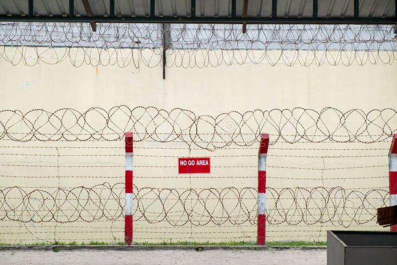 Φράκτης προστασίας με αιχμηρό οδοντωτό - καλώδιο και υψηλός συμπαγής τοίχος στοκ φωτογραφίες με δικαίωμα ελεύθερης χρήσης