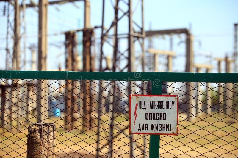 """Φράκτης Rabitz γύρω από τη βιομηχανική ζώνη με το προειδοποιητικό σημάδι """"κάτω από την τάση, κίνδυνος για τη ζωή σας! """" στοκ εικόνα με δικαίωμα ελεύθερης χρήσης"""