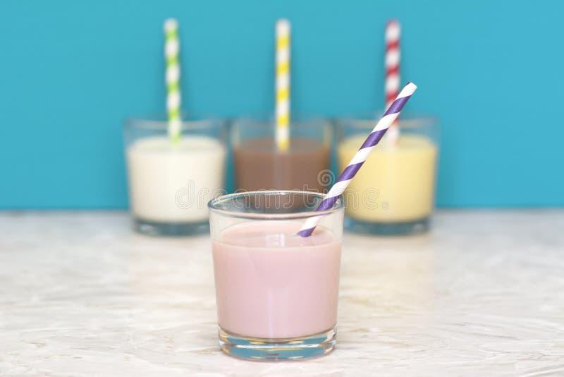 Φράουλα milkshake μπροστά από μια σειρά αρωματικός milkshakes στοκ φωτογραφίες