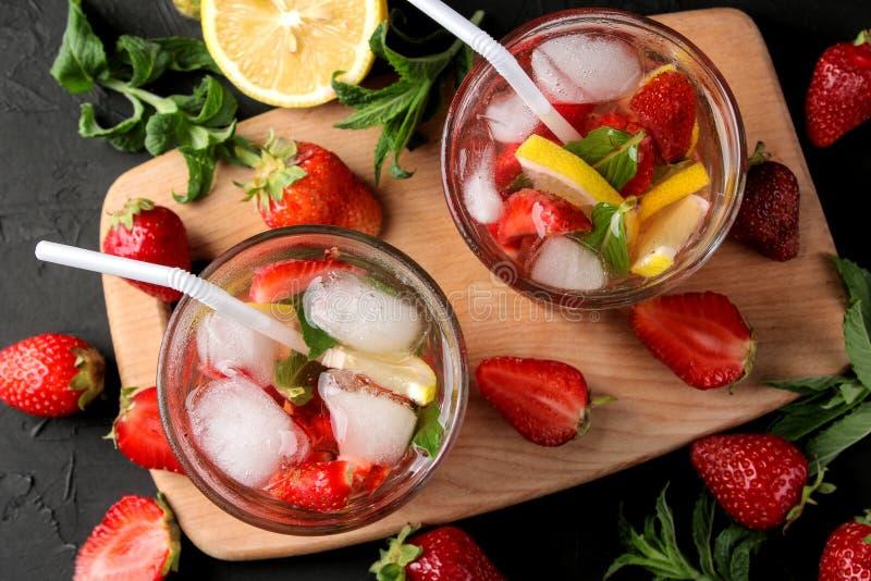 Φράουλα Mojito Κρύο κοκτέιλ θερινού mojito με τις φράουλες, τη μέντα, το λεμόνι και τον πάγο σε ένα γυαλί σε έναν μαύρο πίνακα θε στοκ εικόνες