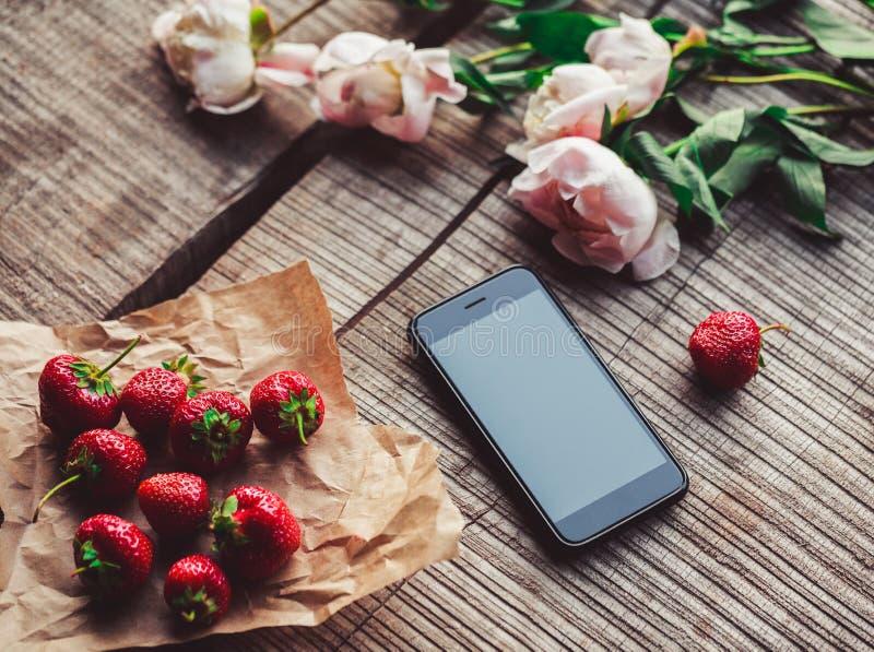 Φράουλες, λουλούδια και τηλέφωνο στον αγροτικό πίνακα Υγιές πρόγευμα, καθαρή κατανάλωση, vegan έννοια τροφίμων στοκ εικόνες