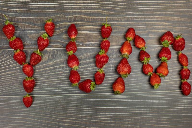 """Φράουλες που κάνουν μια λέξη """"Yum """"στον ξύλινο πίνακα - να κλείσει επάνω στοκ εικόνα με δικαίωμα ελεύθερης χρήσης"""