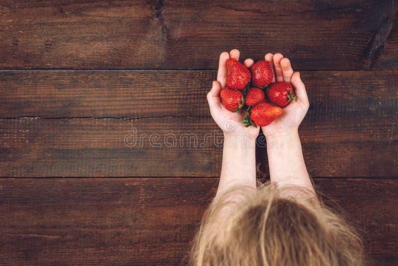 Φράουλες στα χέρια παιδιών Κοριτσάκι στο θερινό καπέλο που κρατά τις φρέσκες κόκκινες οργανικές φράουλες Υπόβαθρο θερινών βιταμιν στοκ εικόνες
