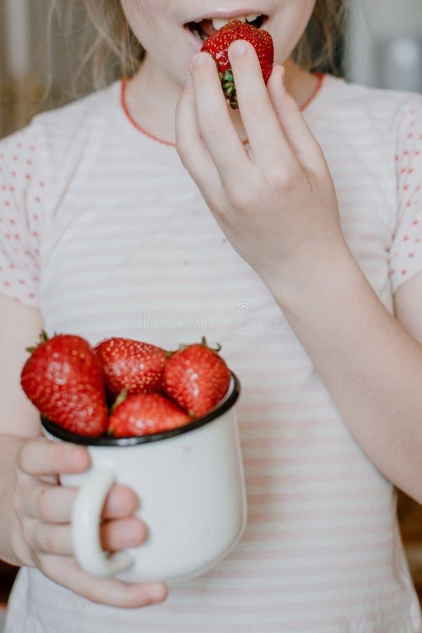 Φράουλες στα χέρια παιδιών Παιδί κοριτσιών που κρατά τις φρέσκες κόκκινες οργανικές φράουλες στο άσπρο σμαλτωμένο φλυτζάνι Θερινέ στοκ φωτογραφία με δικαίωμα ελεύθερης χρήσης